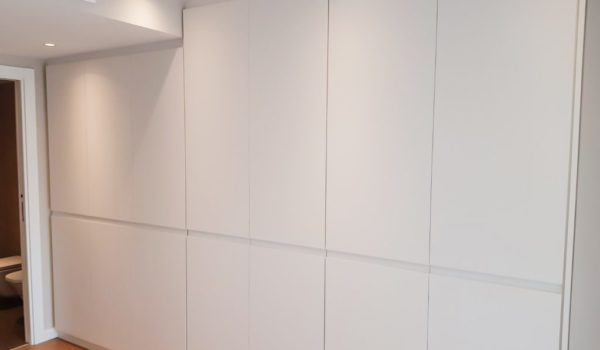 Armari dormitori de terra a sostre lacat blanc mat format per 7 portes partides amb tirador ungler.